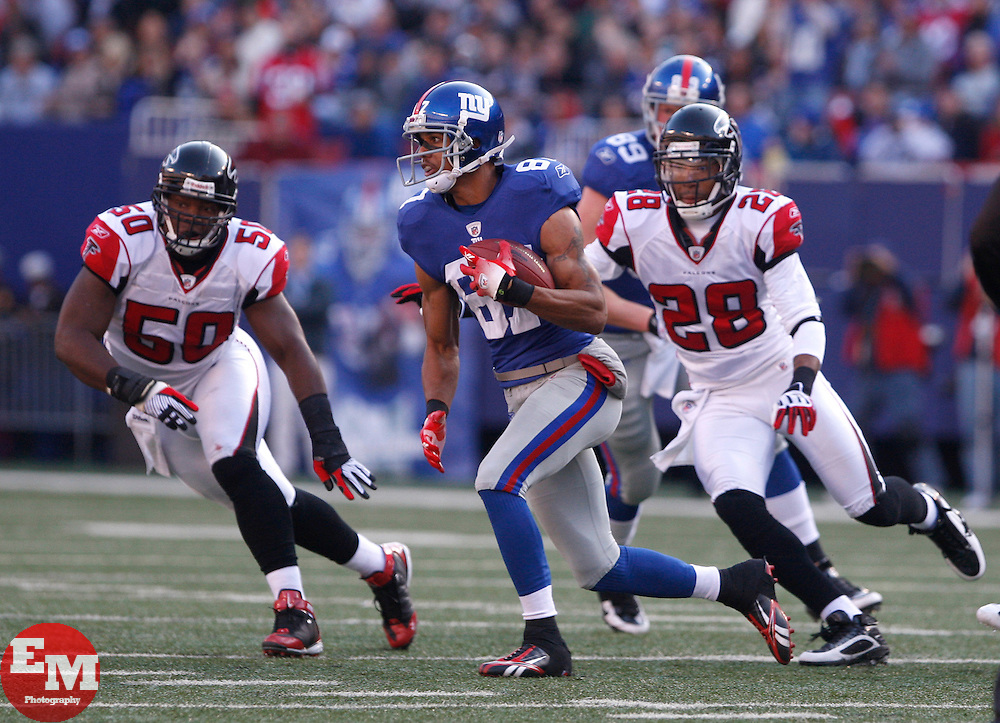 Nov 22, 2009; East Rutherford, NJ, USA; New York Giants wide receiver Domenik Hixon (87) runs away from Atlanta Falcons safety Thomas DeCoud (28) and Atlanta Falcons linebacker Curtis Lofton (50) after a catch during the first half at Giants Stadium. Mandatory Credit: Ed Mulholland