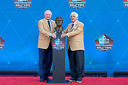 Aug 3, 2019; Canton, OH, USA; Gil Brandt (right) and presenter Jerry Jones  pose with bust of Brandt during the Pro Football Hall of Fame Enshrinement at Tom Benson Hall of Fame Stadium. (Robin Alam/Image of Sport)
