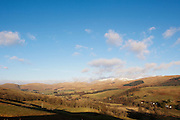 View over green fields with snowy Moffat Hills and blue sky in the background, Annandale Way