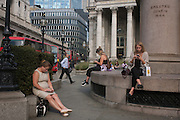 Lunchtime City workers enjoy sunshine near the pillars of Royal Exchange during an unusual autumn heatwave on 13th September 2016, in the City of London, England.