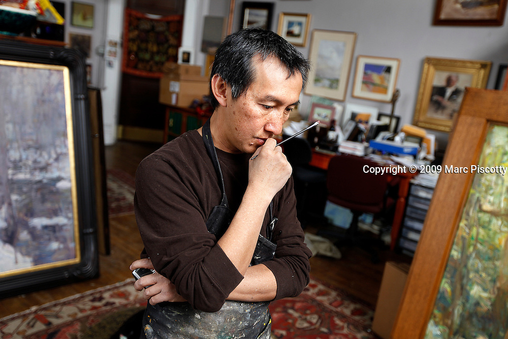 SHOT 12/22/09 1:04:46 PM - Artist Quang Ho, 46, of Littleton, Co. pauses while painting in his studio at the Art Students League of Denver space. Ho specializes in everything from still lifes to landscapes to figures and started drawing as early as age four. He is often kept company while he works by his two basset hounds 'Putter', a three year old male, and 'Birdie', a one and half year old female. (Photo by Marc Piscotty / © 2009)