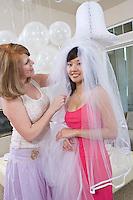 Bridesmaid adjusting bride's veil at bridal shower
