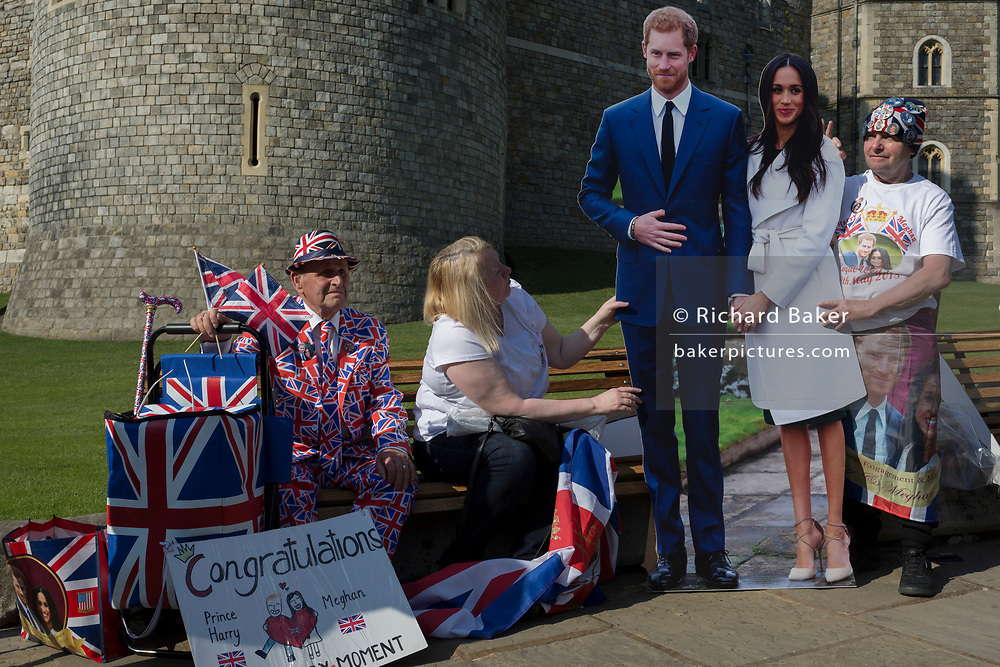 Royalists occupy benches outside Windsor Castle with a life-size standee of Prince Harry and Meghan Markle as the royal town gets ready for the royal wedding between Harry and his American fiance, on 14th May 2018, in London, England.