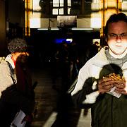 Amsterdam, 11 januari 2014. Man eet een snelle hap op centraal station. Foto: Pepijn Hooimeijer.