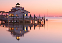 the Roanoke marsh light shines bright in the early morning light as a sailboat floats nearby
