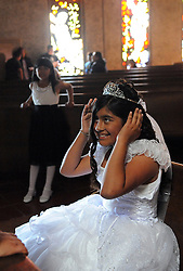 Pamela Ramos, 11, in a white dress after her First Communion ceremony presided over by Father Joey Buena of Madonna del Sasso Church in Salinas. First Communion is an important tradition for Catholic families and individuals.