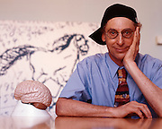 Professor Alan Snyder of The Centre for the Mind at Sydney University with his &quot;think cap&quot;. The pictures on the wall were drawn by four year old autistic children.<br />