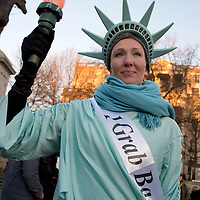 London UK. January 21st 2017.An estimated 100,000 protesters took part in a Women's March from the US Embassy in Grosvenor Square to Trafalgar Square as part of an international campaign on the first full day of Donald Trump's Presidency of the United States. A woman dressed as the Statue of Liberty has a sash which says 'I grab back'.