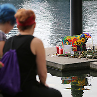 Mourners are seen at a small makeshift memorial at Lake Eola Park flagpole for the victims of the Pulse nightclub where many victims were killed in the deadliest shooting in modern U.S. History on Tuesday, June 14, 2016, in Orlando, Fla. (Alex Menendez via AP)