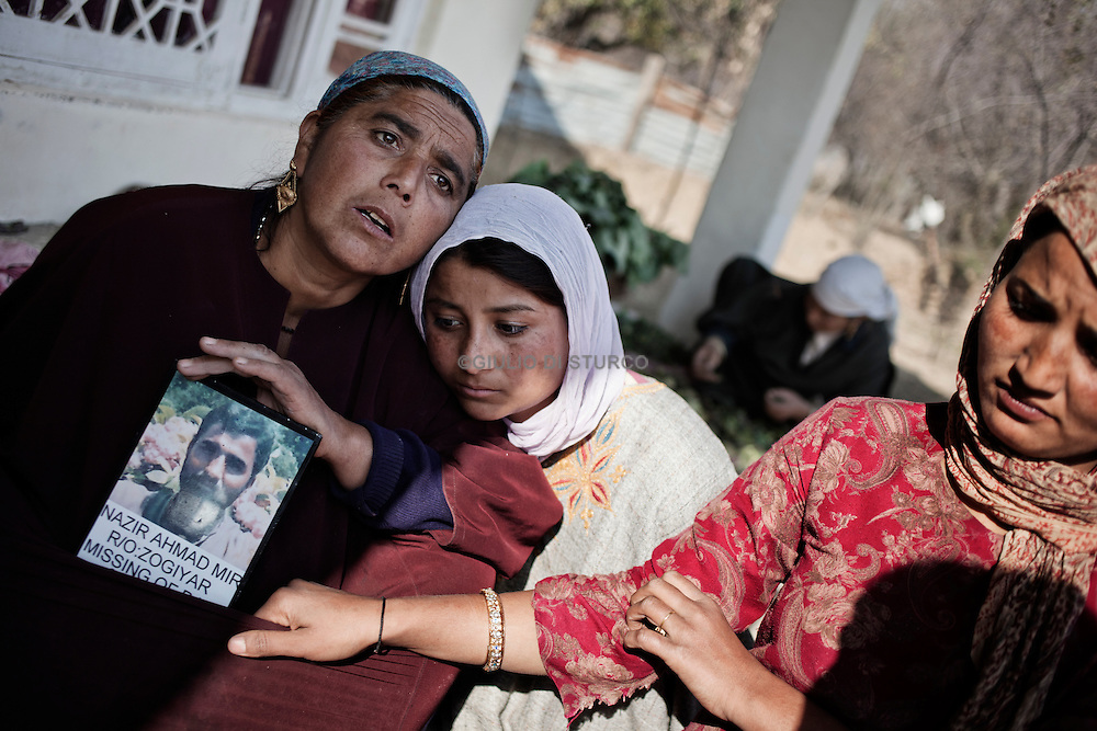 Atega with her two daughters,Talisma (28) and Kolsuma (21), holding the picture of their father disappeared  during the clashes in the 90', 14, November 2010,Zogyar village, Baramulla district, Kashimr.