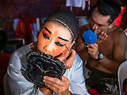 17 FEBRUARY 2016 - BANGKOK, THAILAND: Performers puts on their makeup before a Chinese opera performance in Bangkok. They're with a small troupe that travels from Chinese shrine to Chinese shrine performing for a few nights before going to another shrine. They spend about half the year touring in Thailand and the other half of the year touring in Malaysia. Members of the troupe are paid about 5,000 Thai Baht per month (about $140 US). Chinese opera was once very popular in Thailand, where it is called Ngiew. It is usually performed in the Teochew language. Millions of Chinese emigrated to Thailand (then Siam) in the 18th and 19th centuries and brought their culture with them. Recently the popularity of ngiew has faded as people turn to performances of opera on DVD or movies. There are still as many 30 Chinese opera troupes left in Bangkok and its environs. They are especially busy during Chinese New Year and Chinese holiday when they travel from Chinese temple to Chinese temple performing on stages they put up in streets near the temple, sometimes sleeping on hammocks they sling under their stage. Most of the Chinese operas from Bangkok travel to Malaysia for Ghost Month, leaving just a few to perform in Bangkok.     PHOTO BY JACK KURTZ
