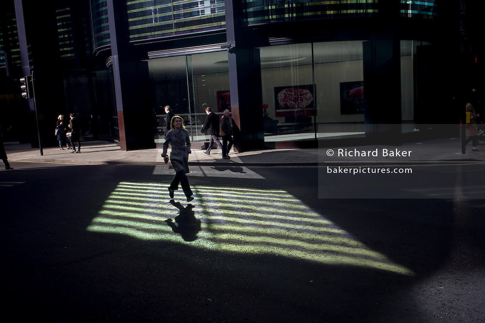 A woman pedestrian runs through green reflected light shining from a City of London office building.