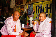 Two burmese woman monk wearing their traditional pink robe and drinking tea