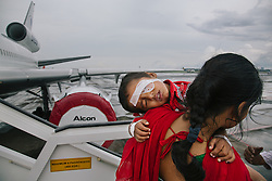 Kolkata, India -- Sunita Singh holds her child, Ayush Singh, as she descends the stairs of the ORBIS DC-10 Aircraft, the world's only airborne ophthalmic training facility. The aircraft offers the latest medical knowledge and training to communities around the world, in order to treat patients and restore sight.