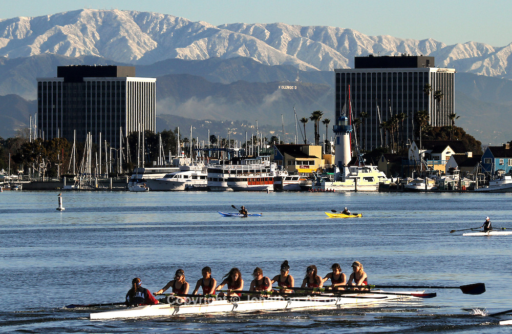 A women's crew team from Loyola Marymount University rows through Marina Del Rey with snowcapped mountains as a backdrop as a cold winter storm moves out of the Southern California area