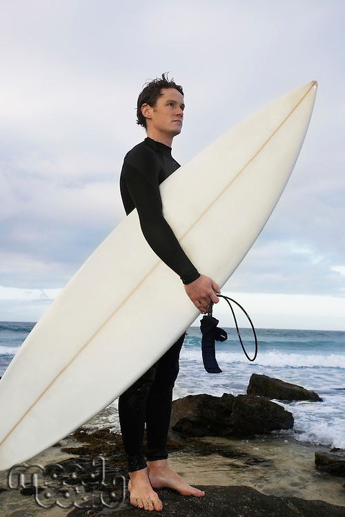 Man holding surfboard on rocks on beach side view
