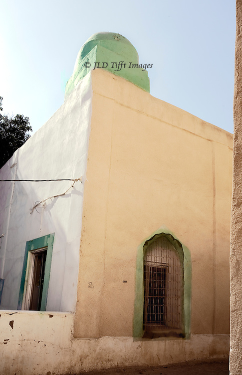 "Oman, mud brick village of Al Hamra, largely abandoned.  Though some structures still endure, no restoration seems to be attempted.  An exception is the mosque with its vestigial ""pillbox"" minaret, carefully maintained. Minaret and doorframe are carefully and freshly painted in green, the Islamic holy color."