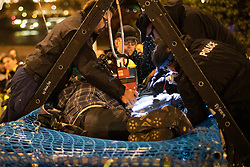 © Licensed to London News Pictures. 07/10/2019. London, UK. A locked on Extinction Rebellion protester is removed from a structure next to Lambeth Bridge . Photo credit: George Cracknell Wright/LNP