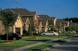 Stock photo of a suburban neighborhood with cars parked in the driveways