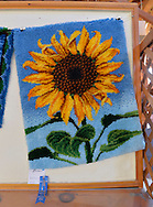 Old Bethpage, New York, U.S. 29th September 2013. This Sunflower design hooked rug by Peter Notarnicola won a FIrst Place blue ribbon from the Agricultural Society of Queens, Nassau and Suffolk Counties at The Long Island Fair. A yearly event since 1842, the county fair is now held at a reconstructed fairground at Old Bethpage Village Restoration.