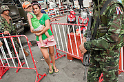 16 MAY 2010 - BANGKOK, THAILAND: Thai civilians who live in the area of the Red Shirt camp leave through a checkpoint manned by Thai troops Sunday. The Thai government is trying to clear the area of civilians ahead of an expected military operation to end the Red Shirt protest. Elsewhere in Bangkok, Thai troops and anti government protesters clashed on Rama IV Road again Sunday afternoon in a series of running battles. Troops fired into the air and unidentified snipers shot at pedestrians on the sidewalks. At one point Sunday the government said it was going to impose a curfew only to rescind the announcement hours later. The situation in Bangkok continues to deteriorate as protests spread beyond the area of the Red Shirts stage at Ratchaprasong Intersection. Many protests now involve people who have not been active in the Red Shirt protests and live in the area of Rama IV. Red Shirt leaders have called for a cease fire, but the government indicated that it is going to go ahead with operations to isolate the Red Shirt camp and clear the streets.      PHOTO BY JACK KURTZ