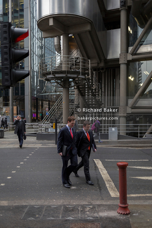 Businessmen walk near Lloyds of London on Lime Street, 7th March 2018 in the City of London, the capital's financial district, 7th March 2018, in London England.