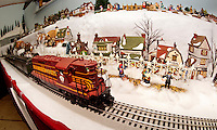 A Boston & Maine locomotive breezes through the Dept. 56 Winter Village scene at the Laconia Antiques Center model train extravaganza  on public display in the upper level.  (Karen Bobotas/for the Laconia Daily Sun)