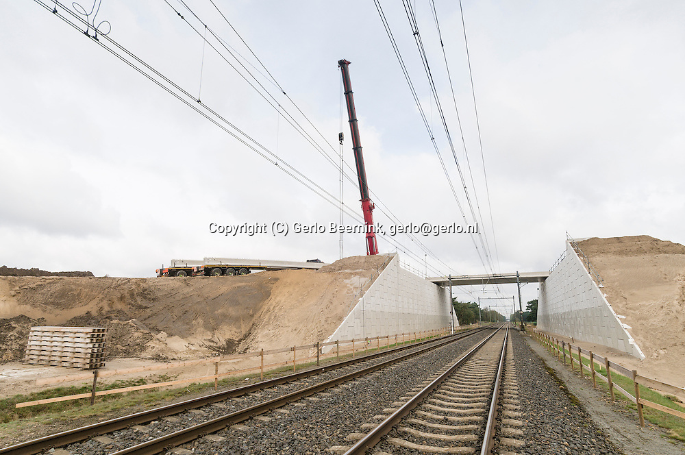 Nederland, Weert, 20130427..Buitendienststelling van het spoor om het dek over het spoor aan te brengen.Aanleg van het ecoduct Weerter-en Budelerbergen, Maarheezerhuttendijk, bij Weert..Prorail legt een ecoduct aan over het spoor Maastricht-Eindhoven en over de er vlakbij liggende snelweg de A2.De bouw van de ecoducten over de spoorlijn Eindhoven-Weert en de A2 vindt plaats in het kader van het Meerjaren Programma Ontsnippering (www.mjpo.nl). Dit is een initiatief van het ministerie van Infrastructuur en Milieu en het ministerie van Economische Zaken, Landbouw en Innovatie. Samen met natuurbeschermingsorganisaties wordt er gewerkt aan het herstellen van verbindingen tussen natuurgebieden. Zoogdieren, amfibiën en reptielen krijgen hierdoor een aanzienlijk groter leefgebied..?Netherlands, Weert, 20130427..Construction of the ecoduct Weerter-en Budelerbergen near Weert.on the motorway A2 and the railway. Weerterbergen