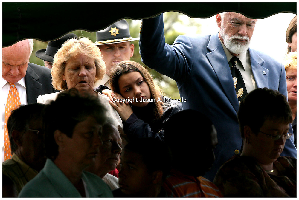 Rena Billeda, age, 13, rests her head on the shoulder of her grandmother Ruth Miller as the two and John Hill listen to the funeral service of Billy Ray Greene. Greene died from injuries after an automobile accident that also claimed the life of Greenville Police Officer Jason Campbell, the first Greenville Police Officer to die in the line of duty since 1952.