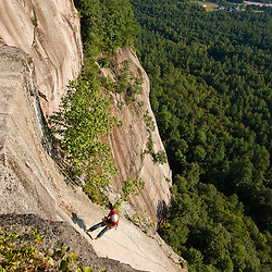 A man rappels from the top of Cathedral Ledge.  Echo Lake State Park in North Conway, New Hampshire.  White Mountains.
