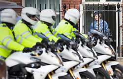 © Licensed to London News Pictures. 11/03/2019. London, UK. Police outriders (L) look round as Prime Minister Theresa May leaves Downing Street by the back door. Mrs May is heading to Westminster Abbey to attend the Commonwealth Day service ahead of tomorrow's crucial Brexit withdrawal vote in Parliament. Photo credit: Peter Macdiarmid/LNP