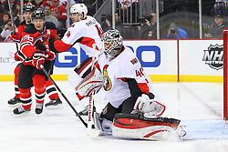 Dec 18, 2013; Newark, NJ, USA;  Ottawa Senators goalie Robin Lehner (40) makes a save while New Jersey Devils left wing Patrik Elias (26) and Ottawa Senators defenseman Chris Phillips (4) look for the rebound during the second period at the Prudential Center.