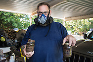 Thomas House holds up samples of soil contaminated with fracking waste he collected from a farmers field after witnessing a truck dump fracking waste on the field. No one was interested in testing his samples becuase he couldn't prove a chain of custody. He keeps them anyway and only handles them when wearing a respirator. House lives approximately 300 Ft from a fracking industry site that often emits toxics fumes in Wellston, Oklahoma.