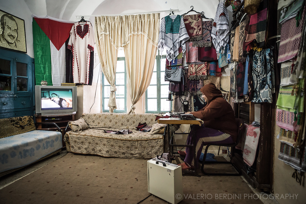 A Palestinian woman,  second wife and mother of the younger child watches TV while works at a sewing machine in one of the last remaining houses bordering the settlers area in Hebron. A heather, a Palestinian flag and her manufacture decorate the room. This resisting family has no intentions to move out of the centre, despite both intimidations and offers of substantial amount of money to purchase the place and relocate.