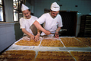 SAFRANBOLU, TURKEY AUGUST 2003. Workers cut and roll the mix for Turkish Delight at the Safrantat factory. The city of Safranbolu positioned in the forests on the Black Sea coast is one of the world heritage sites of the UNESCO. Apart from its Ottoman era wood and mudbrick houses it is also known for its 'Lokum' or Turkish delight. A delicate sweets with flavours from nuts to rose petals. Photo by Frits Meyst/Adventure4ever.com