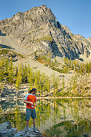 Fisherman trying his luck at Copper Glance Lake in the North Cascades Mountains, Okanogan National Forest Wasington USA