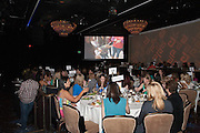 Crowd room atmosphere watching projected program at the Beverly Hilton.