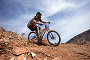 Kyle Strait descends a loose hillside at the 2002 Red Bull Rampage freeride mountain bike competition in Virgin, Utah