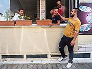 Mehmet says goodbye to men in his neighborhood.