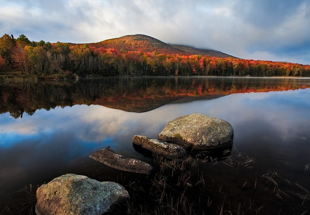 Early morning light illuminates the Autumn colors of a mountain on Seyon Pond in Groton State Forest, Vermont