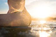 Details of a bikini bottom on a young woman enjoying a sunset paddle with her surfboard at the beach