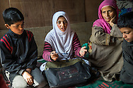 (Alison Griffin to fill in names) (mother's name), (girl's name) and her siblings talk to Save the Children team members about their losses and the devastation for the floods in Abikarpora village on the Dal Lake, Srinagar, Jammu and Kashmir, India, on 25th March 2015. Since the flood, she has been widowed, and is left with four young children and no home. Her family now lives in a temporary shelter built using the emergency shelter kit, and continues their recovery with the help of relief kits such as education kit, food basket, hygiene kit and non-food items from Save the Children. Photo by Suzanne Lee for Save the Children