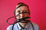 Wired Magazine Executive Editor, Kevin Kelley, in the entry area of his office in San Francisco, California, wrapped in black cables. Model Released.  (1996)