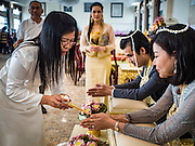 """14 FEBRUARY 2017 - BANGKOK, THAILAND: A couple completes their wedding with a traditional Thai blessing in the Bang Rak district in Bangkok. Bang Rak is a popular neighborhood for weddings in Bangkok because it translates as """"Village of Love."""" (Bang translates as village, Rak translates as love.) Hundreds of couples get married in the district on Valentine's Day, which, despite its Catholic origins, is widely celebrated in Thailand.      PHOTO BY JACK KURTZ"""