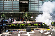 Police shoot tear gas at protesters occupying roads in front of the Central Government Offices, during a protest against a proposed extradition law in Hong Kong, SAR China, on Wednesday, June 12, 2019. Hong Kong's legislative chief postponed the debate on legislation that would allow extraditions to China after thousands of protesters converged outside the chamber demanding the government to withdraw the bill. Photo by Suzanne Lee/PANOS