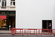 Two construction workmen adopt similar poses with their arms at a project in New Bond Street, London.