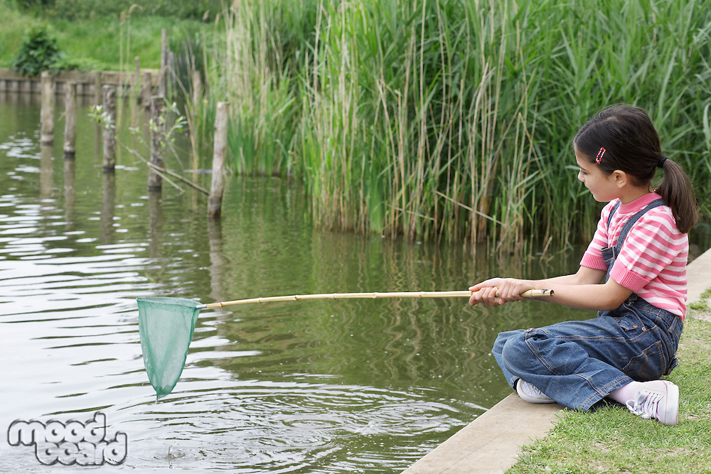 Girl (5-6) with fishing net at river