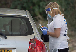 © Licensed to London News Pictures. 19/09/2020. Chessington, UK. A patient receives help during a swab test at a Covid-19 testing centre set up in the car park of Chessington World of Adventures south west of London. The Government have faced criticism over delays in getting tested for the COVID-19 strain of coronavirus. . Photo credit: Peter Macdiarmid/LNP