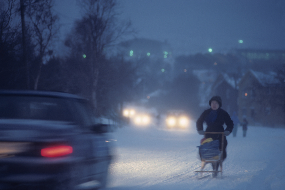 Europe, Norway, Woman pushes wooden cart through early winter snowstorm in arctic coast town of Kirkennes at dusk