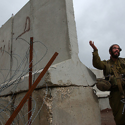 TZIPOREN, ISRAEL, MARCH 2:An Israeli soldier gestures to journalists next to the border with Lebanon near Tziporen army base in north Israel, Sunday, March 2, 2003 as Hezbollah Shiite militants watch from the other side of the fence.  <br />
